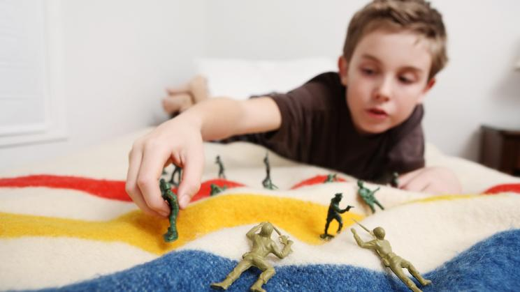 Young boy plays with toy soldiers