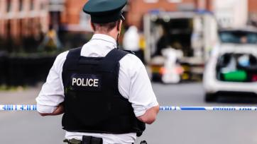 Police officer stands guard at a police cordon point while army ATO defuse a bomb in Belfast, Northern Ireland
