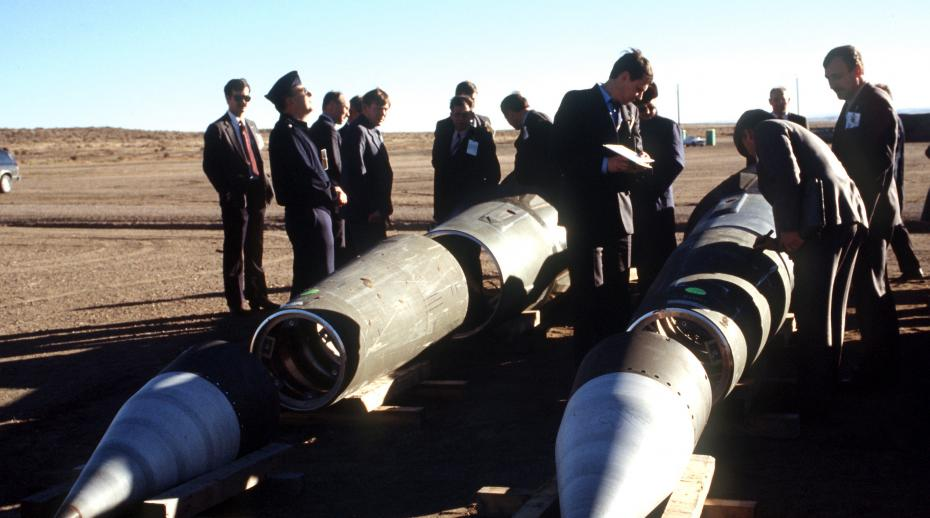 Soviet inspectors and their American escorts stand among several dismantled Pershing II missiles as they view the destruction of other missile components.