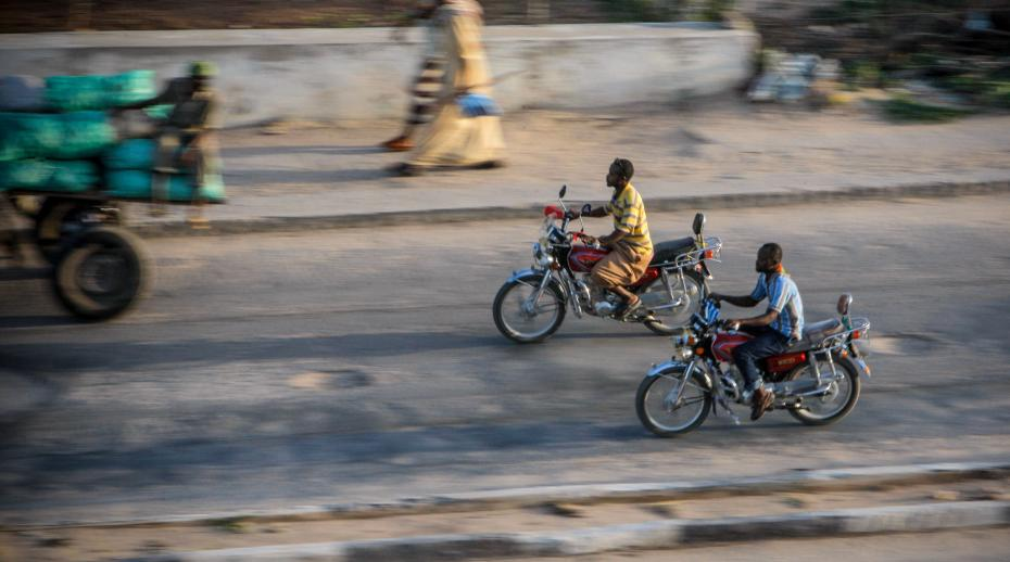 Somali men on motorcycles ride along a road 06 August 2012, opposite the parliament building in the Somali capital Mogadishu.